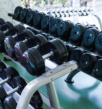 Hanteln m Fitness-Studio, hartes Training mit Kreatin
